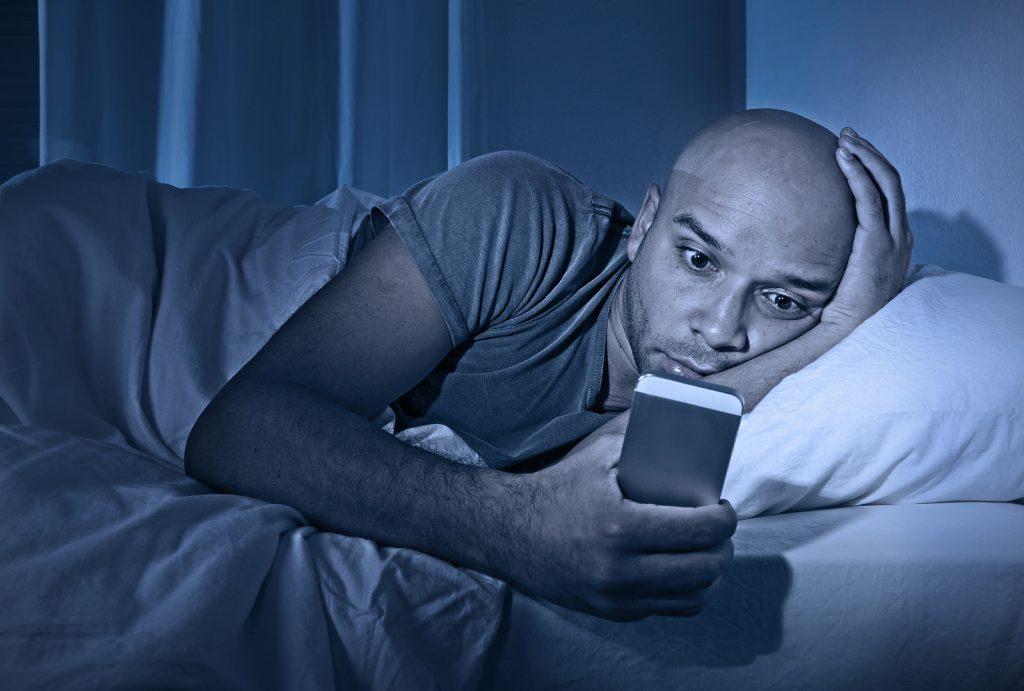 guy trying to sleep on his phone